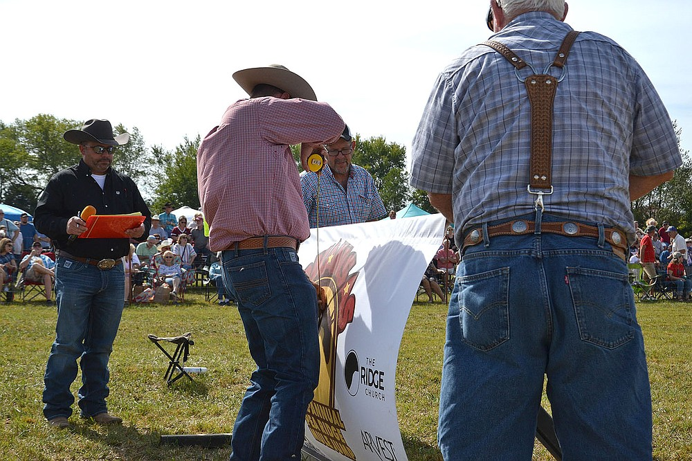 Announcer Jeremy Weir of Siloam Springs, left, watches to see how high the jump will be that Harold and Don Shockley are raising as judge Allen McBurnett measures at the 32nd annual Pea Ridge Mule Jump.