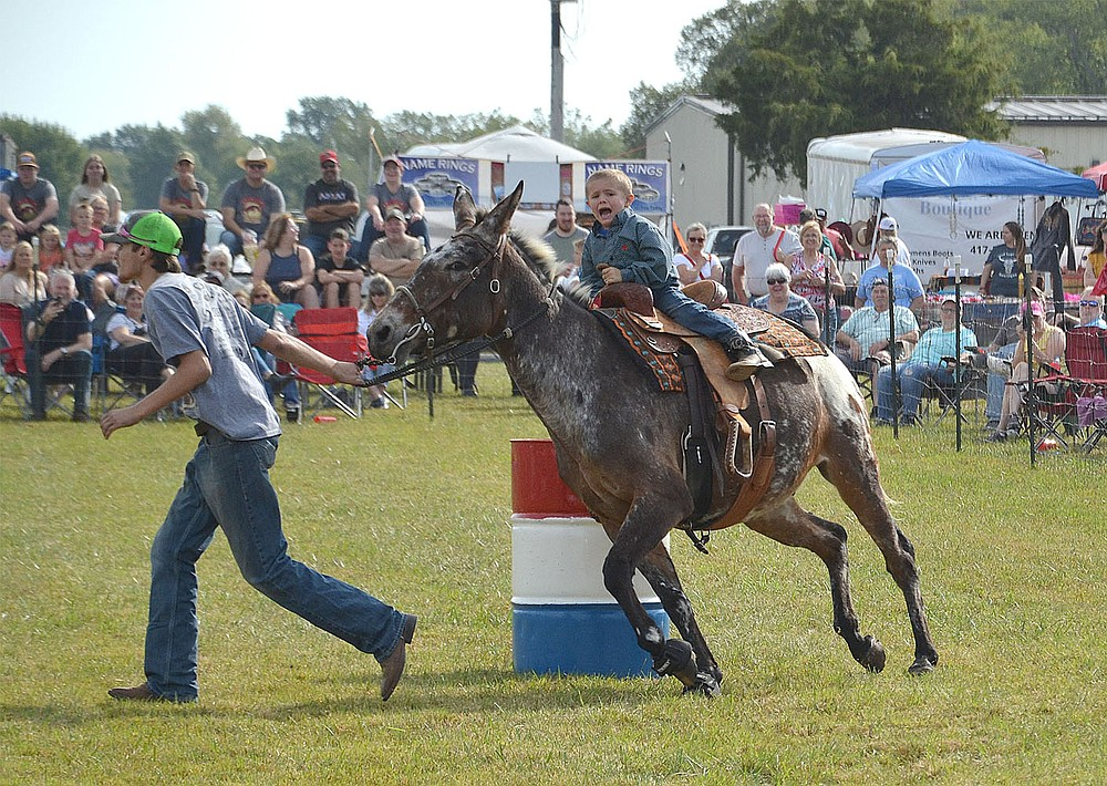 A small boy rides the mule through the barrel race while being led around the course.