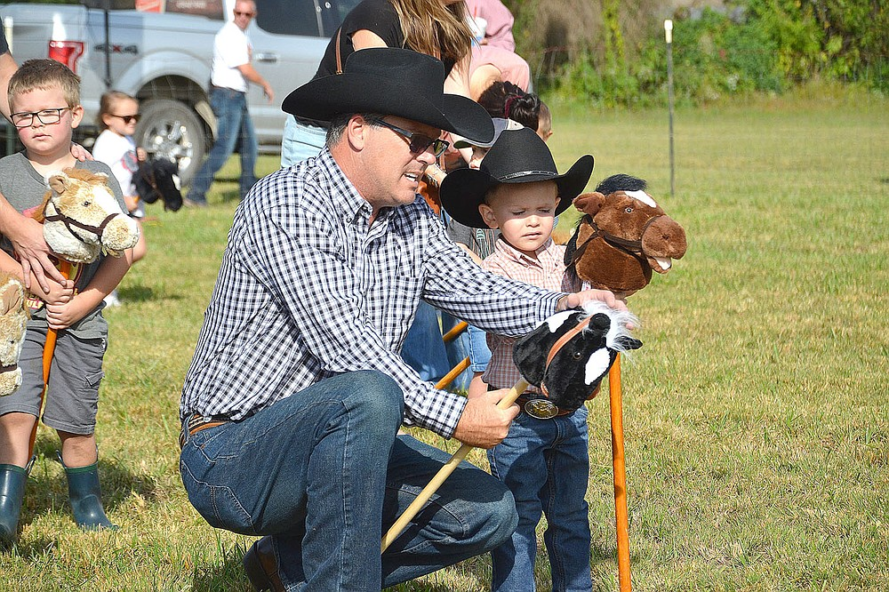 David McCord of Lowell, helped his grandson Joseph Tattoo, 3, with the stick mule race Saturday at the 32nd annual Pea Ridge Mule Jump.