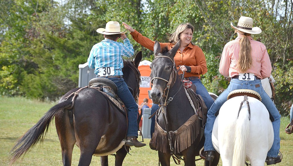 Becki Sams, whose father Joe Sams was a long-time competitor at the mule jump, visits with fellow mule riders Saturday while waiting her turn for the arena.