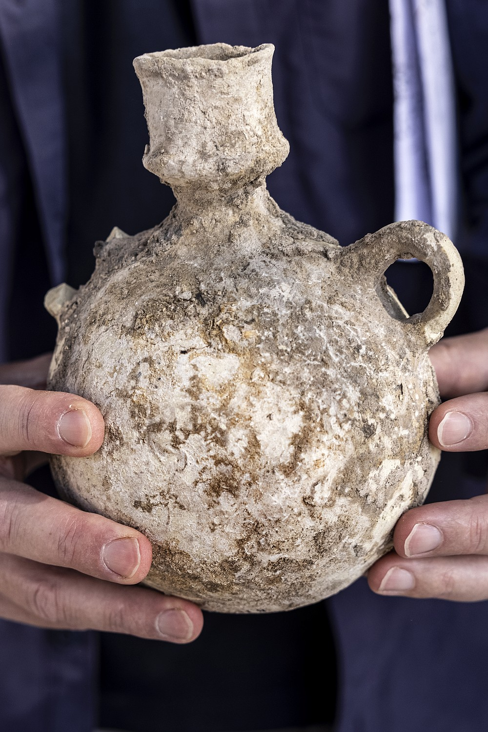 An Israel Antiquities Authority employe holds a jar from a massive ancient winemaking complex dating back some 1,500 years in Yavne, central, Israel, Monday, Oct. 11, 2021. Israeli archaeologists said the complex includes five wine presses, warehouses, kilns for producing clay storage vessels and tens of thousands of fragments and jars. (AP Photo/Tsafrir Abayov)
