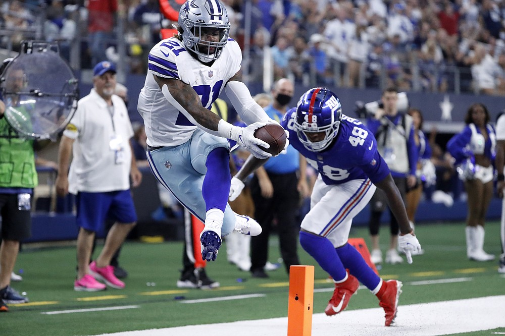 Dallas Cowboys running back Ezekiel Elliott (21) reaches into the end zone to score a touchdown after getting through New York Giants linebacker Tae Crowder (48) in the second half of an NFL football game in Arlington, Texas, Sunday, Oct. 10, 2021. (AP Photo/Roger Steinman)