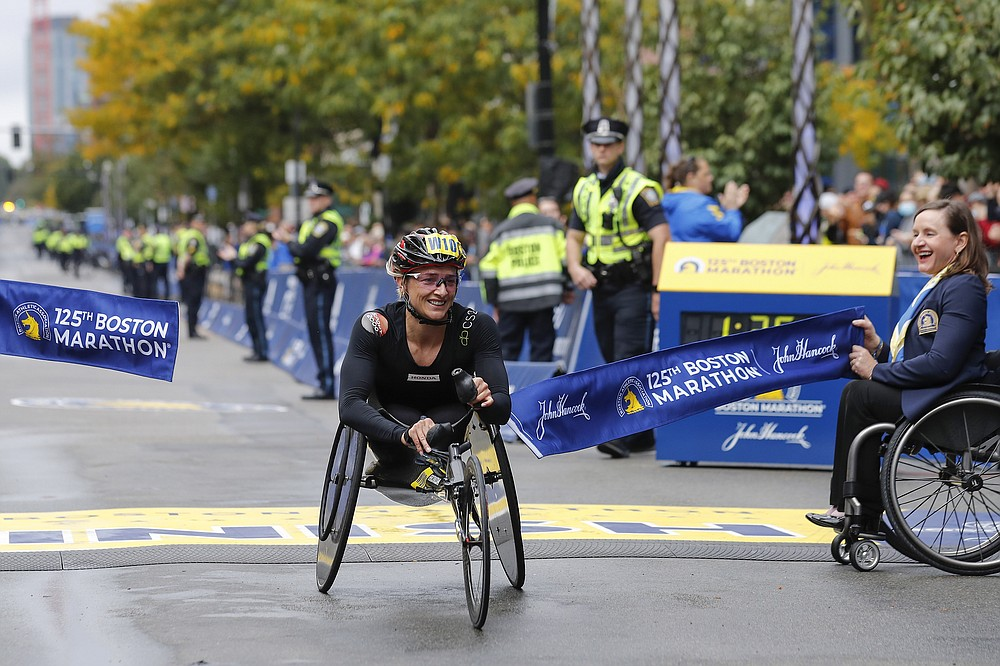 Manuela Schar, of Switzerland, breaks the tape to win the women's wheelchair division of the 125th Boston Marathon Monday, Oct. 11, 2021, in Boston. (AP Photo/Winslow Townson)