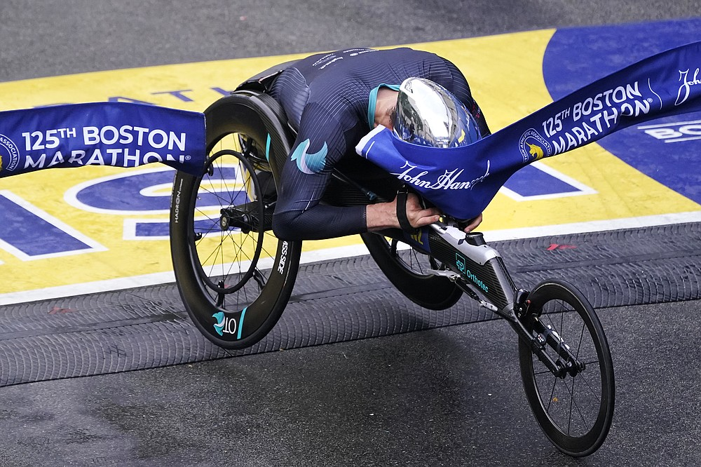 Marcel Hug, of Switzerland, breaks the finish line with his helmet to win the men's wheelchair division at the Boston Marathon in Boston, Monday, Oct. 11, 2021. (AP Photo/Charles Krupa)