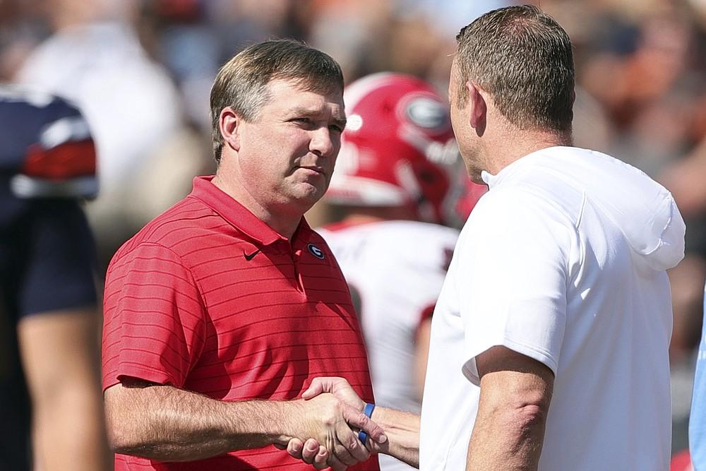 Georgia head coach Kirby Smart and Auburn head coach Bryan Harsin shake hands before the first half of an NCAA college football game Saturday, Oct. 9, 2021, in Auburn, Ala. (AP Photo/Butch Dill)