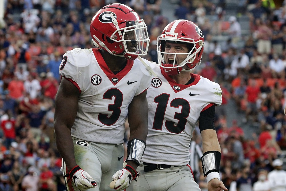 Georgia running back Zamir White (3) celebrates with quarterback Stetson Bennett (13) after scoring a touchdown against Auburn during the second half of an NCAA college football game Saturday, Oct 9, 2021 in Auburn, Al. (AP Photo/Butch Dill)