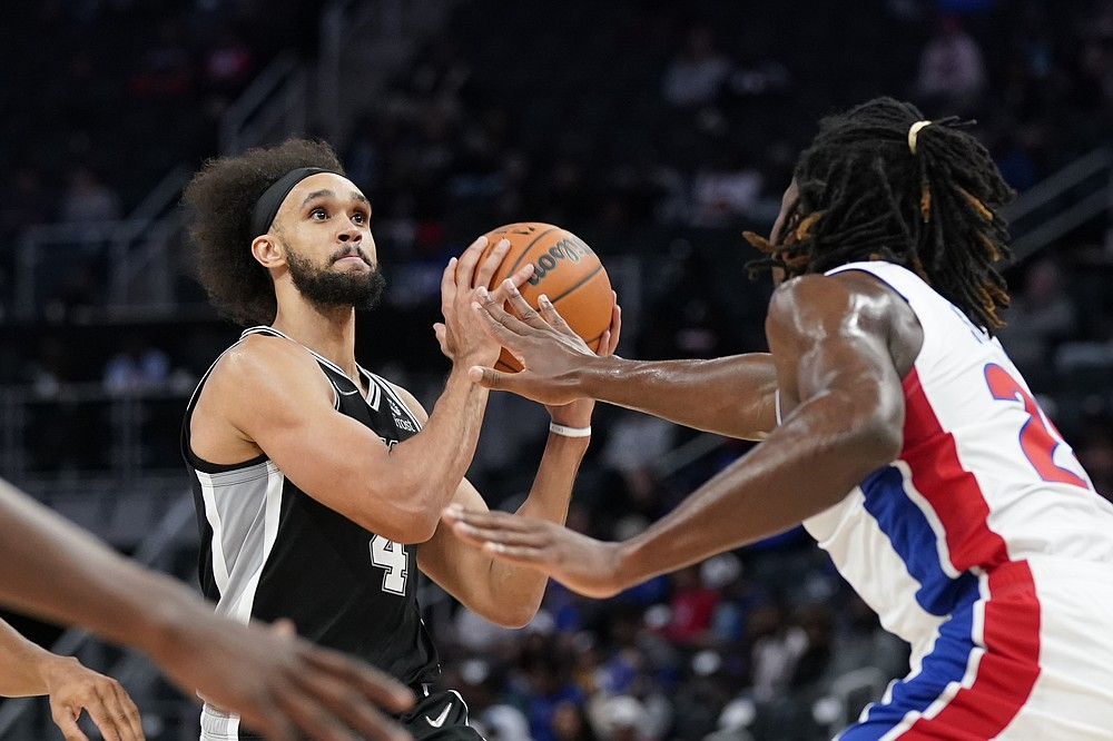 San Antonio Spurs guard Derrick White (4) is defended by Detroit Pistons center Isaiah Stewart during the first half of a preseason NBA basketball game, Wednesday, Oct. 6, 2021, in Detroit. (AP Photo/Carlos Osorio)