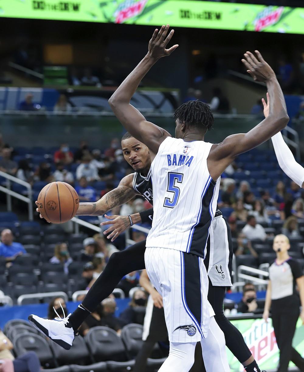 San Antonio Spurs guard Dejounte Murray, left, passes the ball behind Orlando Magic center Mo Bamba's back during the second half of an a preseason NBA basketball game, Sunday, Oct. 10, 2021, in Orlando, Fla. (AP Photo/Jacob M. Langston)