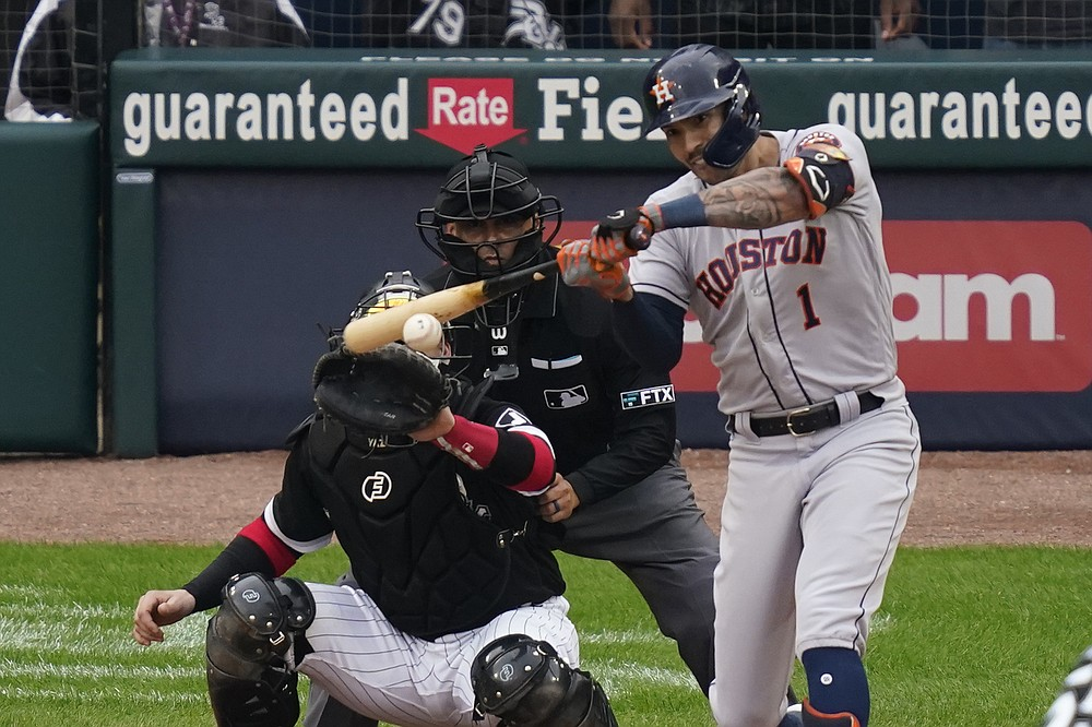 Houston Astros' Carlos Correa hits a two-run double against the Chicago White Sox in the third inning during Game 4 of a baseball American League Division Series Tuesday, Oct. 12, 2021, in Chicago. (AP Photo/Charles Rex Arbogast)