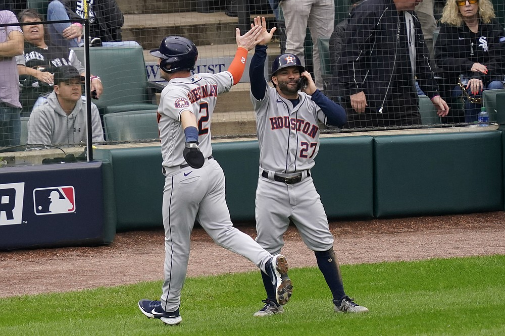 Houston Astros' Alex Bregman (2) and Jose Altuve (27) celebrate scoring on a Carlos Correa double against the Chicago White Sox in the third inning during Game 4 of a baseball American League Division Series Tuesday, Oct. 12, 2021, in Chicago. (AP Photo/Charles Rex Arbogast)