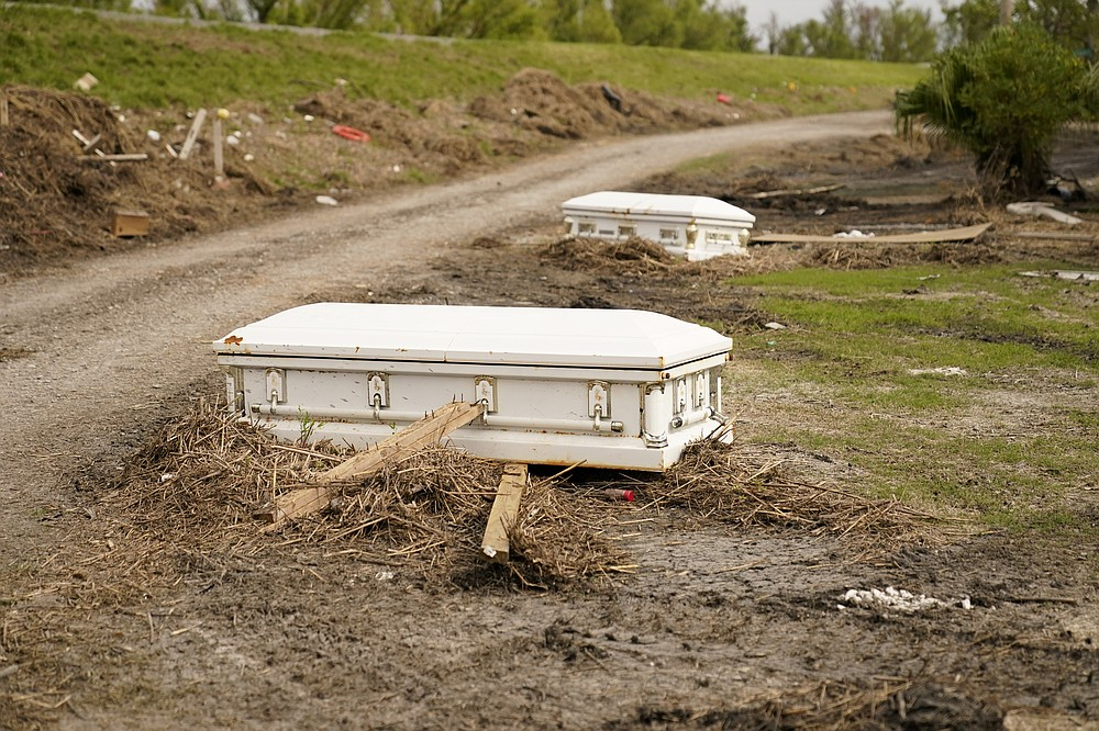 Caskets that floated from their tombs during flooding from Hurricane Ida, sit along a roadside in Ironton, La., Monday, Sept. 27, 2021. Hurricane Ida swept through Louisiana with furious winds that ripped roofs off buildings and storm surge so powerful it moved homes. And what it wrought on the living it also wrought on the dead, moving vaults and caskets and adding another layer of trauma on families and communities recovering from the powerful storm. (AP Photo/Gerald Herbert)