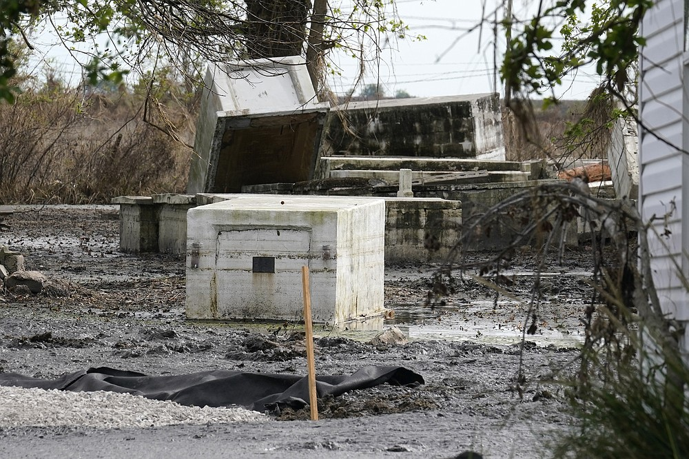 Tombs damaged from flooding from Hurricane Ida sit atop one another in Ironton, La., Monday, Sept. 27, 2021. Hurricane Ida swept through Louisiana with furious winds that ripped roofs off buildings and storm surge so powerful it moved homes. And what it wrought on the living it also wrought on the dead, moving vaults and caskets and adding another layer of trauma on families and communities recovering from the powerful storm. (AP Photo/Gerald Herbert)