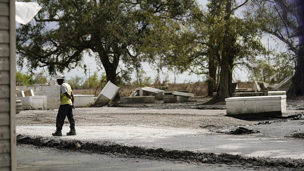 A worker walks through a heavily damaged cemetery in Ironton, La., Monday, Sept. 27, 2021. A Louisiana task force is working to gather vaults and caskets disrupted from their burial sites by Hurricane Ida and rebury them. (AP Photo/Gerald Herbert)