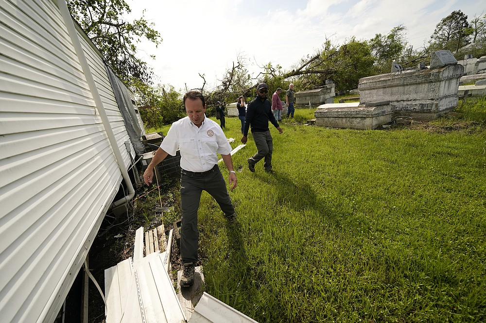 Louisiana Attorney General Jeff Landry walks through a cemetery during a survey after Hurricane Ida, in LaPlace, La., Wednesday, Sept. 22, 2021. A Louisiana task force is working to gather vaults and caskets disrupted from their burial sites by Hurricane Ida and rebury them. (AP Photo/Gerald Herbert)