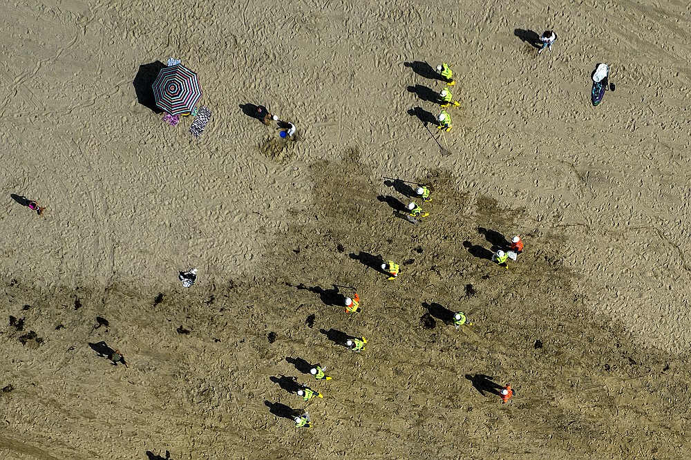This aerial photo shows beachgoers as workers in protective suits continue to clean the contaminated beach in Huntington Beach, Calif., Monday, Oct. 11, 2021. Huntington Beach reopened its shoreline this morning after water testing results came back with non-detectable amounts of oil associated toxins in ocean water, city officials and California State Parks announced. (AP Photo/Ringo H.W. Chiu)
