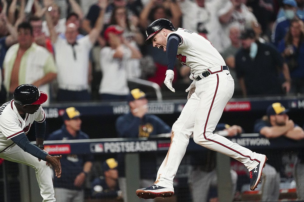 Atlanta Braves' Freddie Freeman, right, celebrates his solo homerun during the eighth inning of Game 4 of a baseball National League Division Series against the Milwaukee Brewers, Tuesday, Oct. 12, 2021, in Atlanta. (AP Photo/John Bazemore)