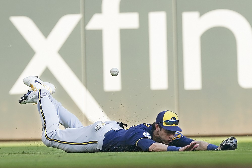 Milwaukee Brewers left fielder Christian Yelich (22) dives the for the ball hit by Atlanta Braves' Adam Duvall during the second inning of Game 4 of a baseball National League Division Series, Tuesday, Oct. 12, 2021, in Atlanta. Duvall made it to first base on the hit.(AP Photo/John Bazemore)