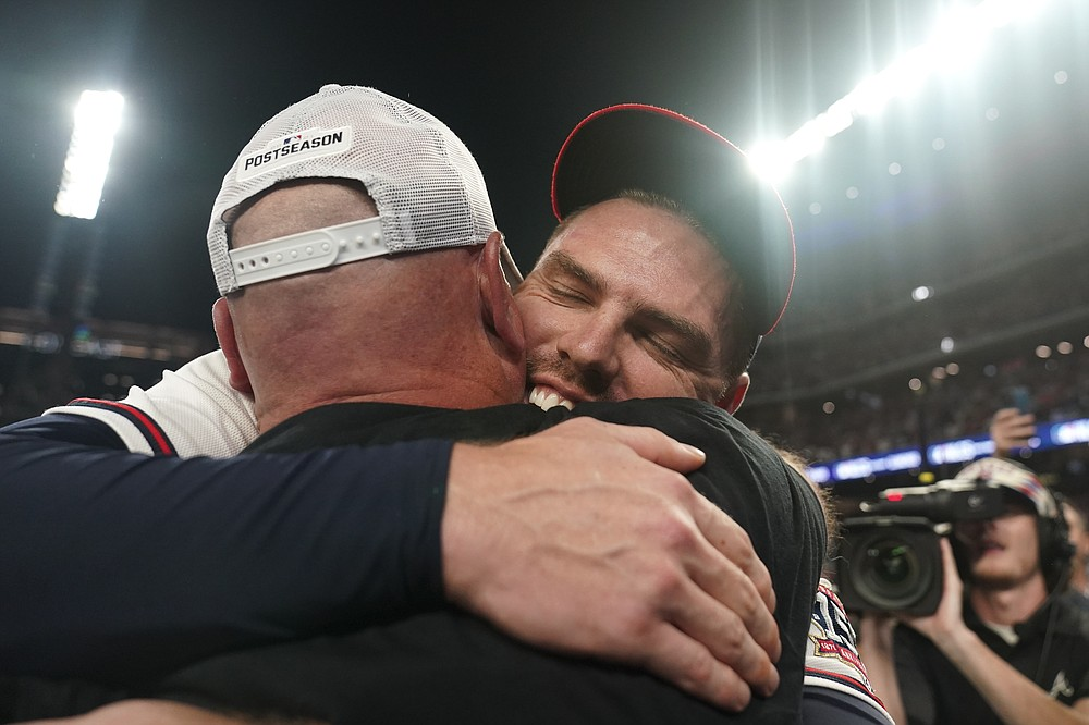 Atlanta Braves Freddie Freeman embraces Atlanta Braves manager Brian Snitker after Game 4 of a baseball National League Division Series against the Milwaukee Brewers, Tuesday, Oct. 12, 2021, in Atlanta. The Atlanta Braves won 5-4 to advance to the NLCS. (AP Photo/Brynn Anderson)