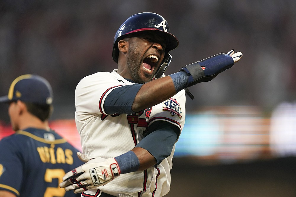 Atlanta Braves' Guillermo Heredia (38) celebrates an two RBI single hit by Atlanta Braves' Eddie Rosario during the fourth inning of Game 4 of a baseball National League Division Series against the Milwaukee Brewers, Tuesday, Oct. 12, 2021, in Atlanta. (AP Photo/Brynn Anderson)