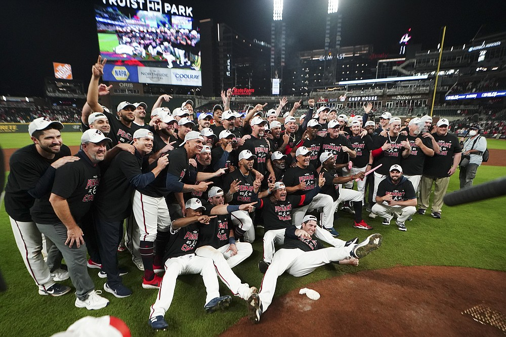 The Atlanta Braves pose fopr a photo after Game 4 of a baseball National League Division Series against the Milwaukee Brewers, Tuesday, Oct. 12, 2021, in Atlanta. The Atlanta Braves won 5-4 to advance to the NCLS. (AP Photo/John Bazemore)