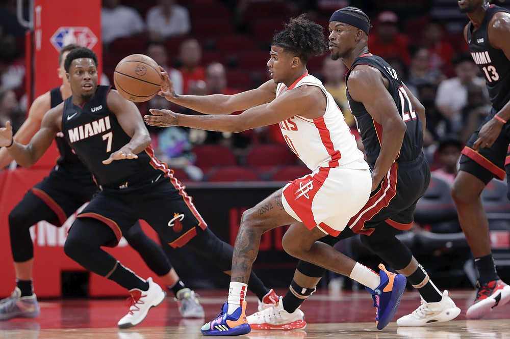 Houston Rockets guard Jalen Green, center, passes the ball between Miami Heat guard Kyle Lowry (7) and forward Jimmy Butler, right, during the first half of an NBA preseason basketball game Thursday, Oct. 7, 2021, in Houston. (AP Photo/Michael Wyke)