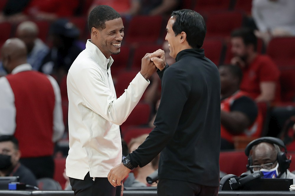 Houston Rockets coach Stephen Silas, left, and Miami Heat head coach Erik Spoelstra bump fists after the Heat's 113-106 win in an NBA preseason basketball game Thursday, Oct. 7, 2021, in Houston. (AP Photo/Michael Wyke)