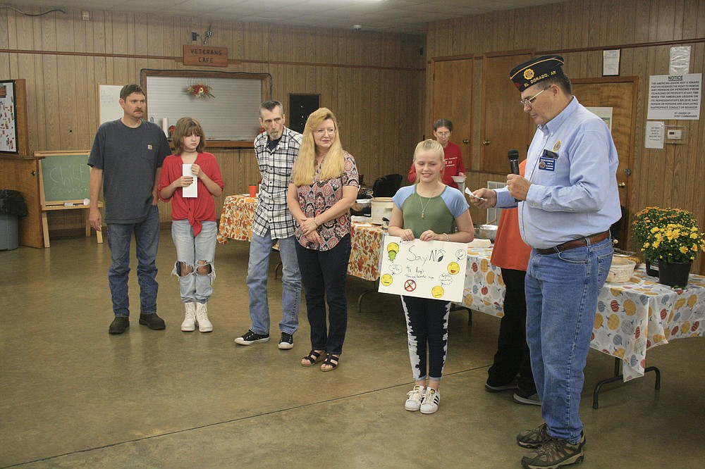 """Rebekah Ibert, second to left, and Loren Freeman, second to right, both accepted awards on Tuesday evening from American Legion Post 10 Commander Brian Burdine, right, for the winning posters they made for the state's """"War on Drugs"""" poster contest. (Matt Hutcheson/News-Times)"""