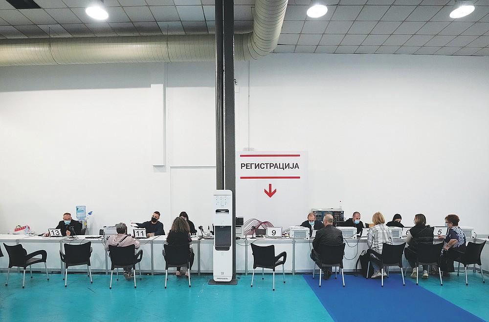 People fill out vaccination consent forms at Belgrade Fair makeshift vaccination center in Belgrade, Serbia, Saturday, Oct. 2, 2021. (AP Photo/Darko Vojinovic)