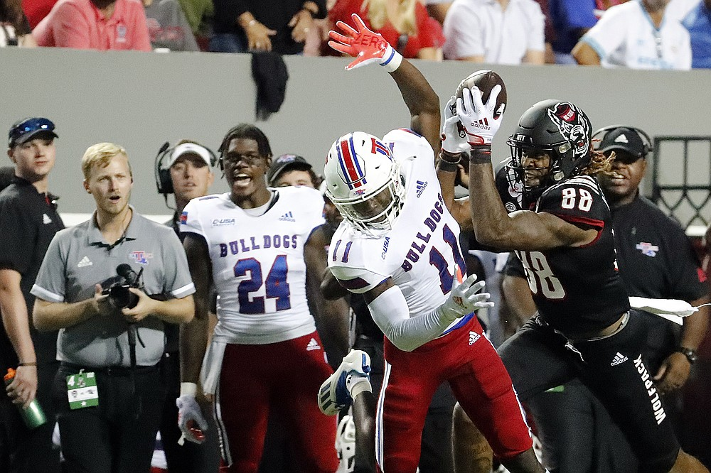 North Carolina State's Devin Carter (88) hauls in a pass in front of Louisiana Tech's Cedric Woods (11) during the first half of an NCAA college football game in Raleigh, N.C., Saturday, Oct. 2, 2021. (AP Photo/Karl B DeBlaker)