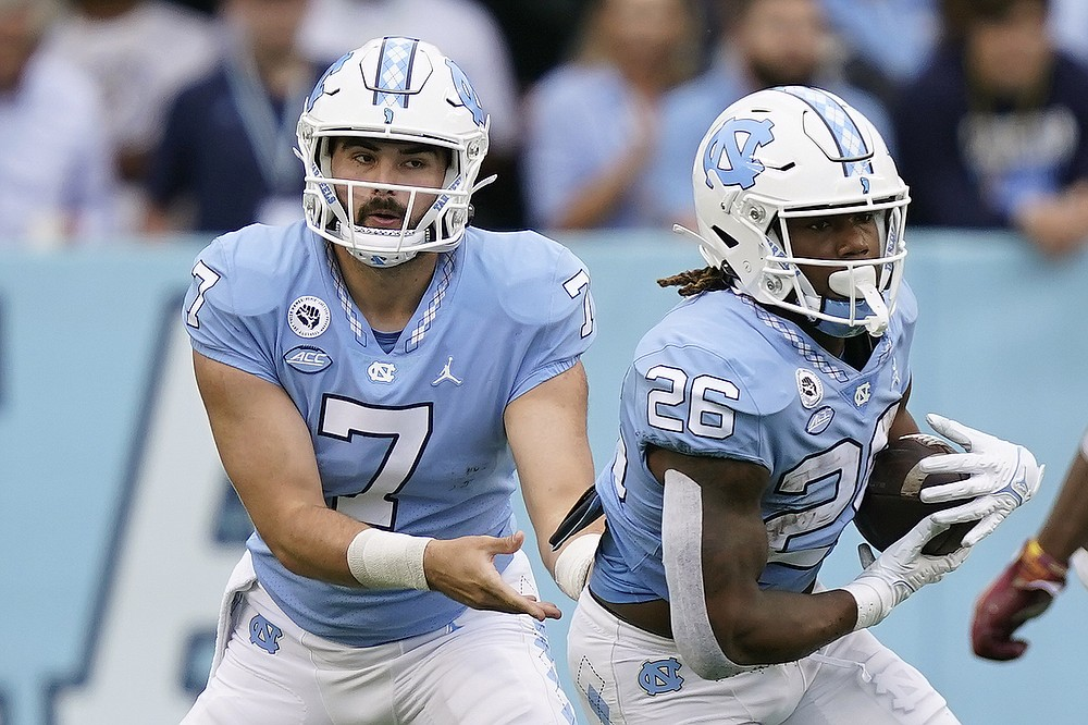 North Carolina quarterback Sam Howell (7) hands off to running back D.J. Jones (26) during the first half of an NCAA college football game against Florida State in Chapel Hill, N.C., Saturday, Oct. 9, 2021. (AP Photo/Gerry Broome)