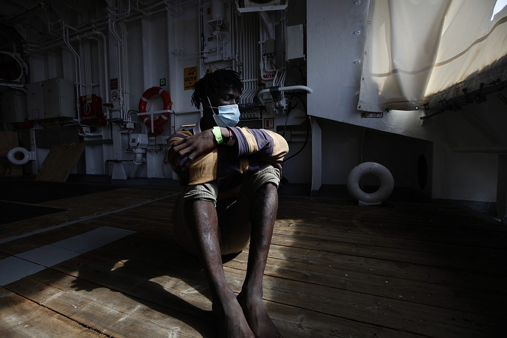 Mohamed Salah, a migrant from Ivory Coast, sits on the deck of the rescue vessel Geo Barents waiting for his disembarkation at the port of Augusta, on the island of Sicily, Italy, Monday, Sept. 27, 2021. Salah is among tens of thousands of migrants who have endured torture, sexual violence and extortion at the hands of guards in detention centers in Libya, a major hub for migrants fleeing poverty and wars in Africa and the Middle East, hoping for a better life in Europe. (AP Photo/Ahmed Hatem)