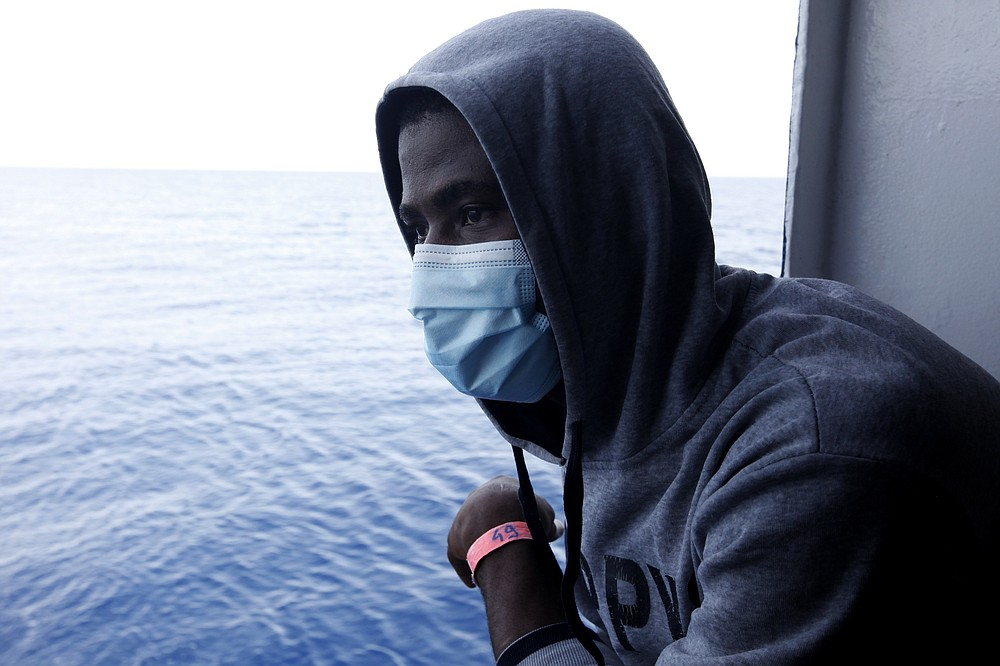 Guinean migrant Amadou Traoré looks at the Mediterranean as he awaits disembarkation at the port of Augusta, on the island of Sicily, Italy, Monday, Sept. 27, 2021. Traoré  and other migrants say they were tortured and their families extorted for ransoms in Libya's detention centers. Their accounts to The Associated Press come as a report commissioned by the United Nations said last week that suspected crimes against humanity have been committed against migrants intercepted at sea and turned over to Libya's detention centers. (AP Photo/Ahmed Hatem)