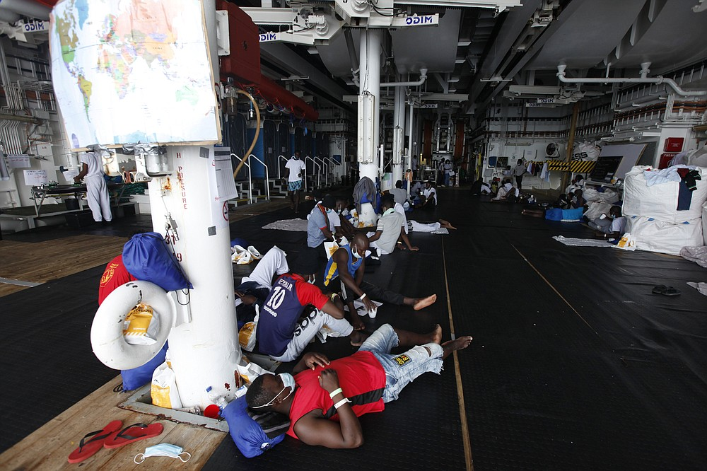 African migrants await disembarkation at the port of Augusta, on the island of Sicily, Italy, Monday, Sept. 27, 2021. The migrants, who were rescued off the coast of Libya, say they were tortured and their families extorted for ransoms in Libya's detention centers. Their accounts to The Associated Press come as a report commissioned by the United Nations said last week that suspected crimes against humanity have been committed against migrants intercepted at sea and turned over to Libya's detention centers. (AP Photo/Ahmed Hatem)