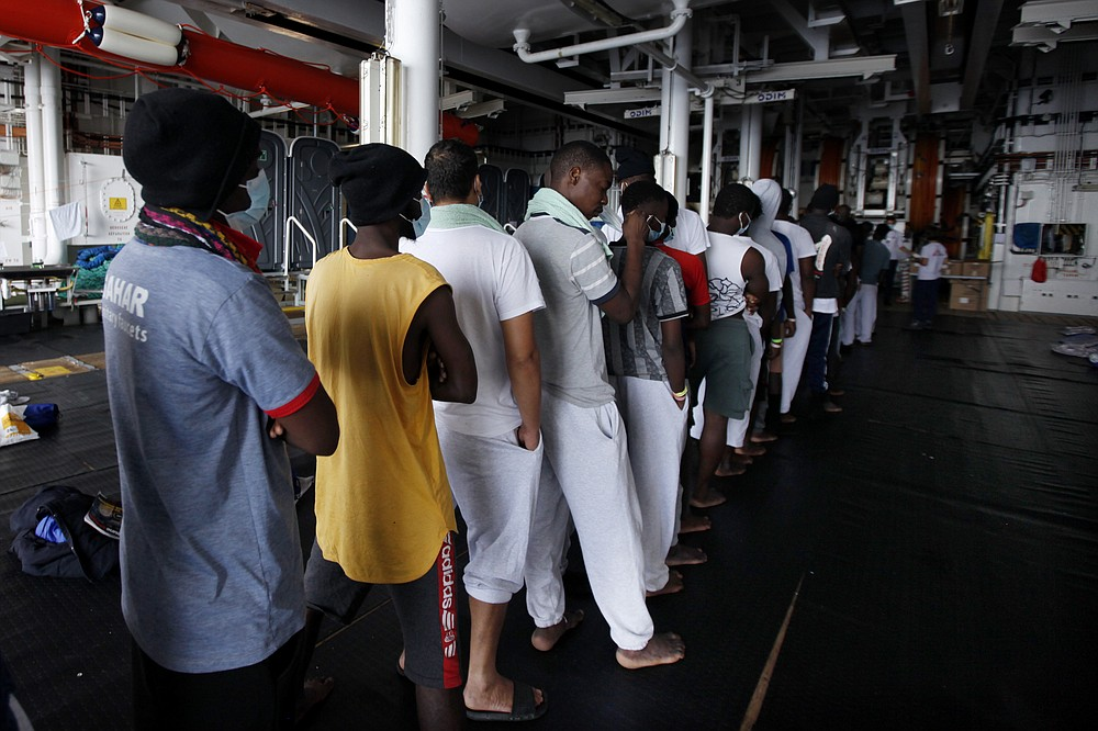 African migrants wait in line to receive meals abroad the Geo Barents vessel after they were rescued from the Mediterranean Sea off Libya, Monday, Sept. 27, 2021. Migrants say that they were tortured and their families extorted for ransoms in Libya's detention centers. (AP Photo/Ahmed Hatem)
