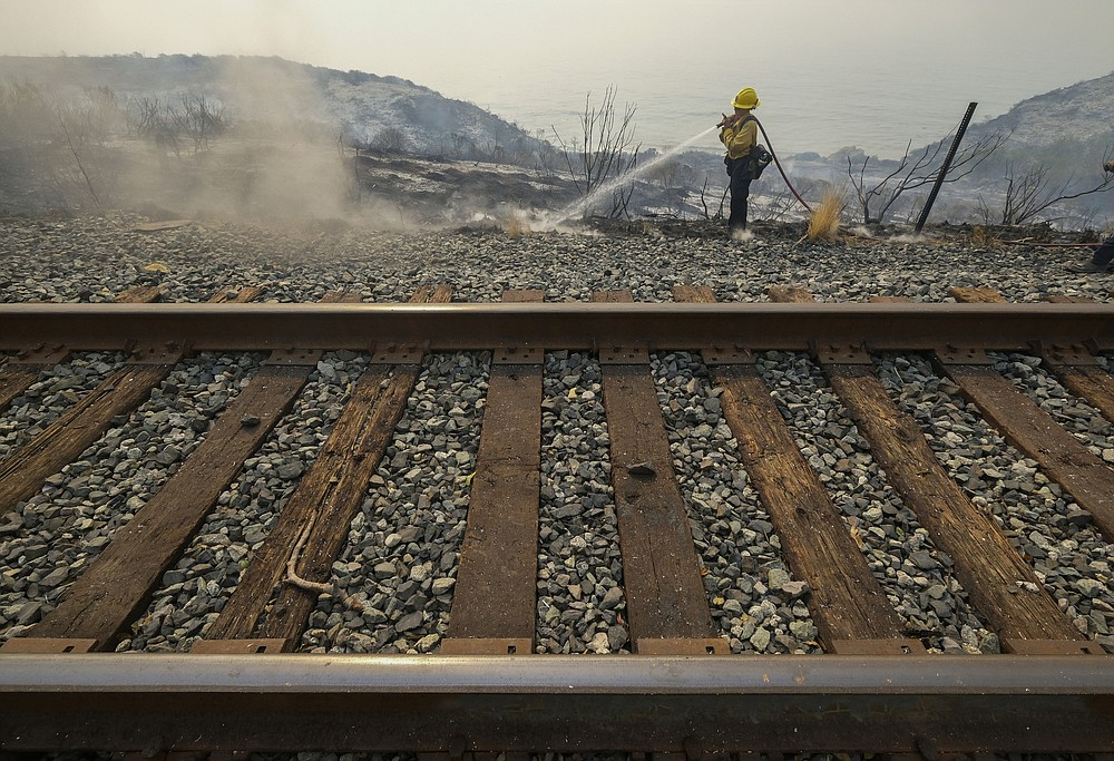 County of Santa Barbara Fire Department firefighters extinguish a roadside fire next to train tracks off of the U.S. 101 highway Wednesday, Oct. 13, 2021, in Goleta, Calif. A wildfire raging through Southern California coastal mountains threatened ranches and rural homes and kept a major highway shut down Wednesday as the fire-scarred state faced a new round of dry winds that raise risk of flames. The Alisal Fire covered more than 22 square miles (57 square kilometers) in the Santa Ynez Mountains west of Santa Barbara. (AP Photo/Ringo H.W. Chiu)