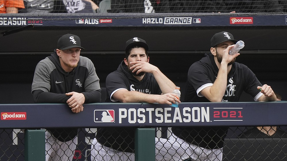 Chicago White Sox pitcher Carlos Rodon, center, watches from the dugout with Andrew Vaughn, left, and Lucas Giolito against the Houston Astros in the third inning during Game 4 of a baseball American League Division Series Tuesday, Oct. 12, 2021, in Chicago. (AP Photo/Nam Y. Huh)