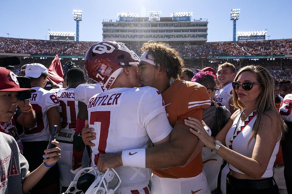 Oklahoma quarterback Spencer Rattler hugs Texas quarterback Casey Thompson after Oklahoma beat Texas in an NCAA college football game at the Cotton Bowl, Saturday, Oct. 9, 2021, in Dallas. (AP Photo/Jeffrey McWhorter)