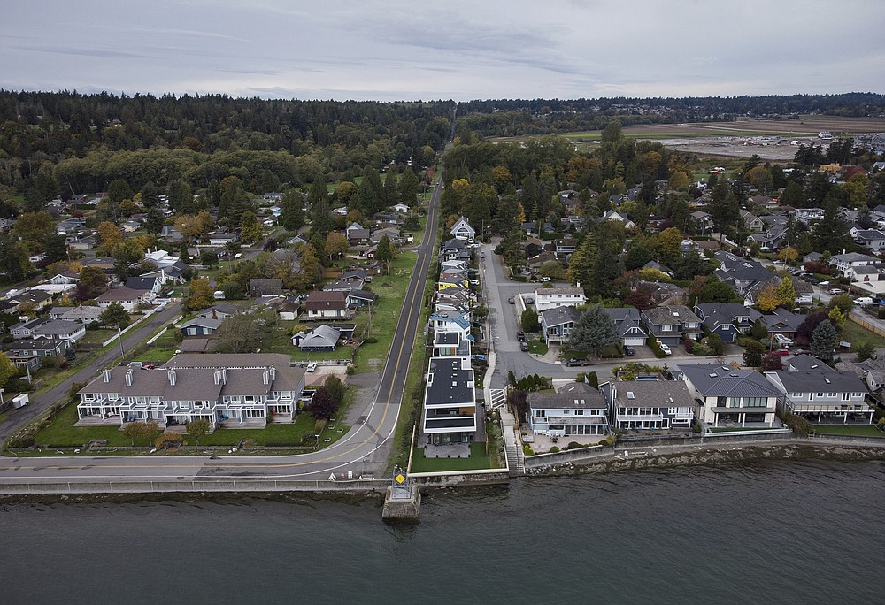 Homes in Delta, British Columbia, left, and Point Roberts, Wash., right, are separated by the Canada-U.S. border which is just north of Roosevelt Way in Point Roberts, as seen in an aerial view on Wednesday, Oct. 13, 2021. Point Roberts sits on a peninsula and is only accessible by land by travelling through Canada. Beleaguered business owners and families separated by COVID-19 restrictions rejoiced Wednesday after the U.S. said it will reopen its land borders to nonessential travel next month, ending a 19-month freeze. (Darryl Dyck/The Canadian Press via AP)