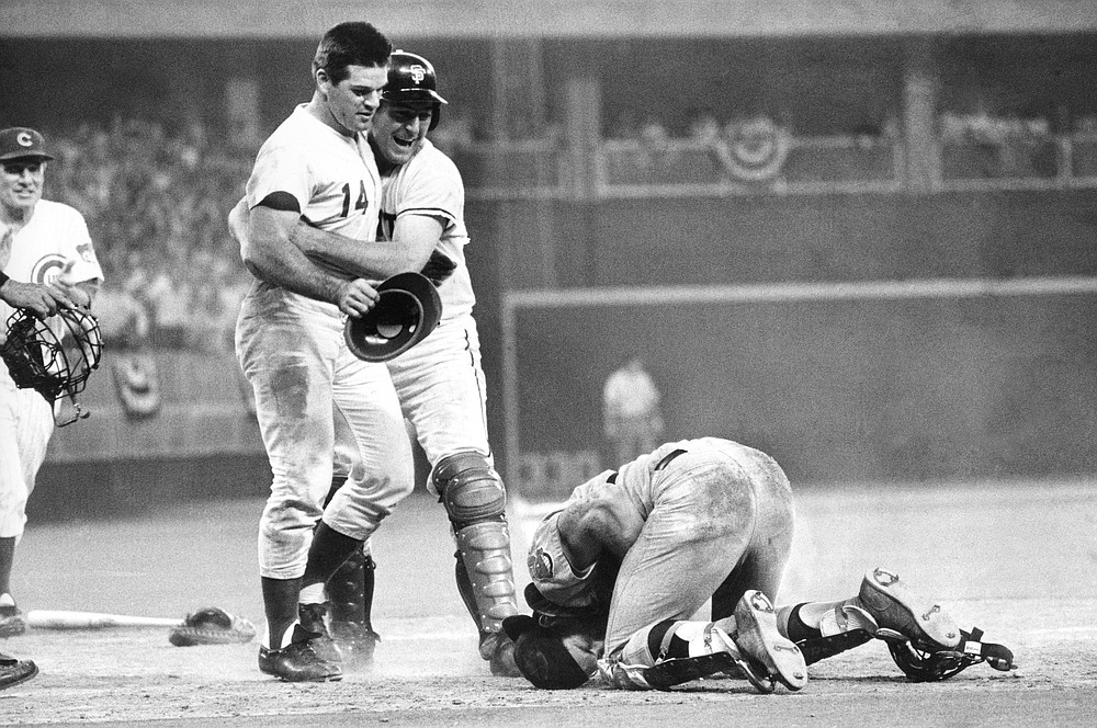 FILE - In this July 14, 1970, file photo, National League's Pete Rose, left, is hugged by teammate Dick Dietz while American League catcher Ray Fosse lies injured on the ground, after Rose crashed into Fosse to score the game-winning run in the baseball All-Star Game in Cincinnati. Fosse, the strong-armed catcher whose career was upended when he was bowled over by Rose in the All-Star Game, has died. He was 74. Carol Fosse, his wife of 51 years, said in a statement Fosse died Wednesday, Oct. 13, 2021, after a 16-year bout with cancer. (AP Photo, File)
