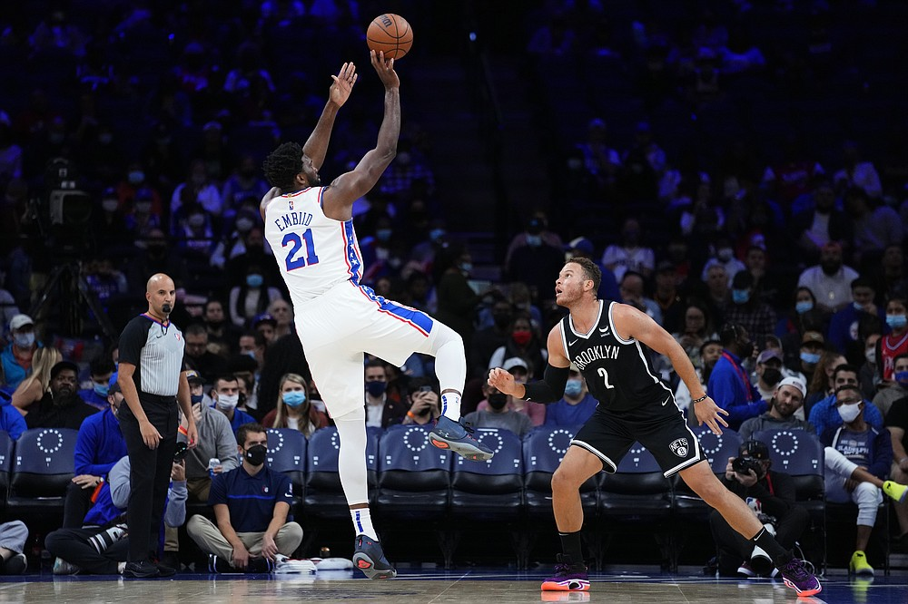 Philadelphia 76ers' Joel Embiid, left, goes up for a shot against Brooklyn Nets' Blake Griffin during the first half of a preseason NBA basketball game, Monday, Oct. 11, 2021, in Philadelphia. (AP Photo/Matt Slocum)