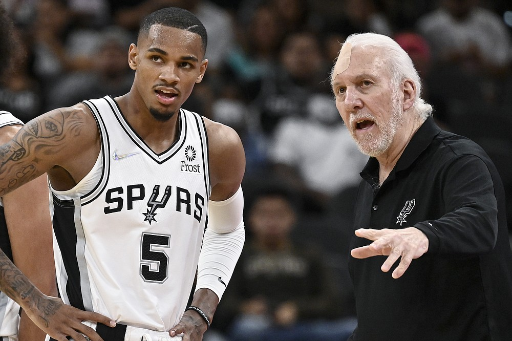 San Antonio Spurs head coach Gregg Popovich, right, talks with Spurs guard Dejounte Murray during the second half of a preseason NBA basketball game against the Miami Heat, Friday, Oct. 8, 2021, in San Antonio. (AP Photo/Darren Abate)